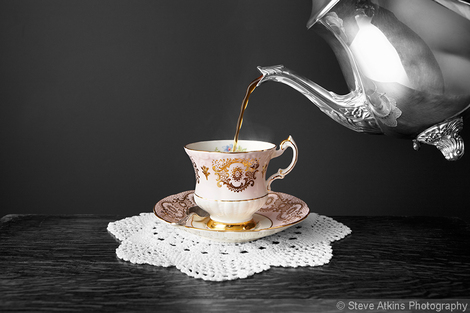 Pouring tea into a vintage fine bone china teacup from a silver teapot photo